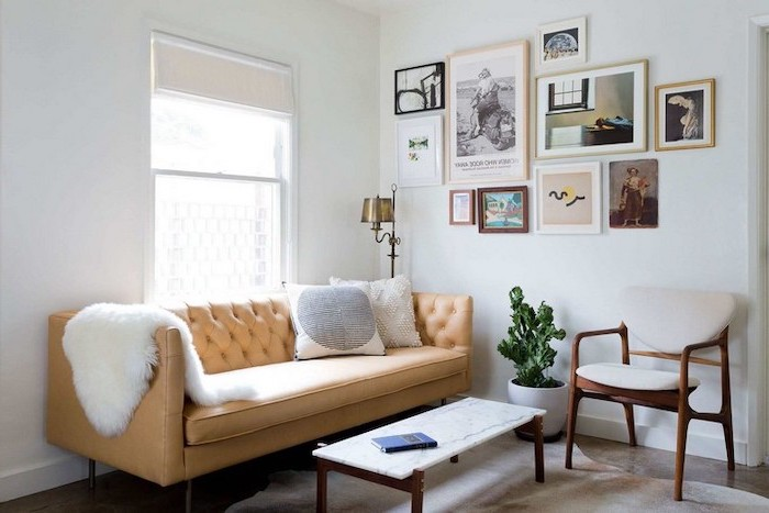 small room decor, brown leather couch, wood and marble, coffee table, hanging art, white walls