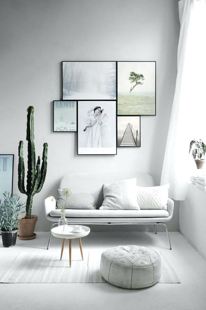 living room arrangements, white sofa, hanging art, white ottoman and rug, potted plants, small coffee table