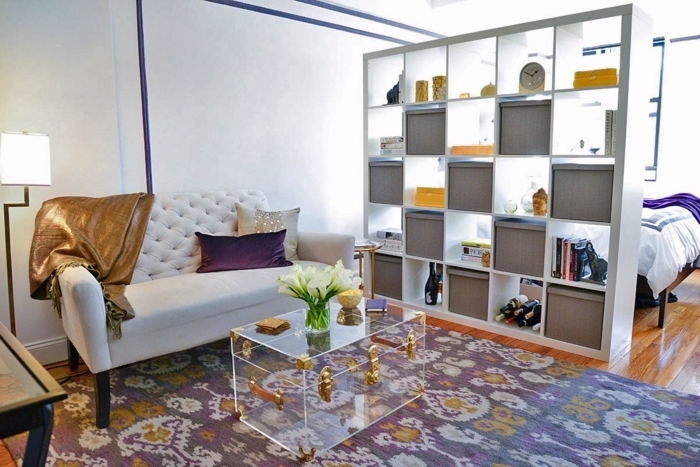 white bookshelf divider, white sofa, glass coffee table, in the shape of a suitcase, living room arrangements