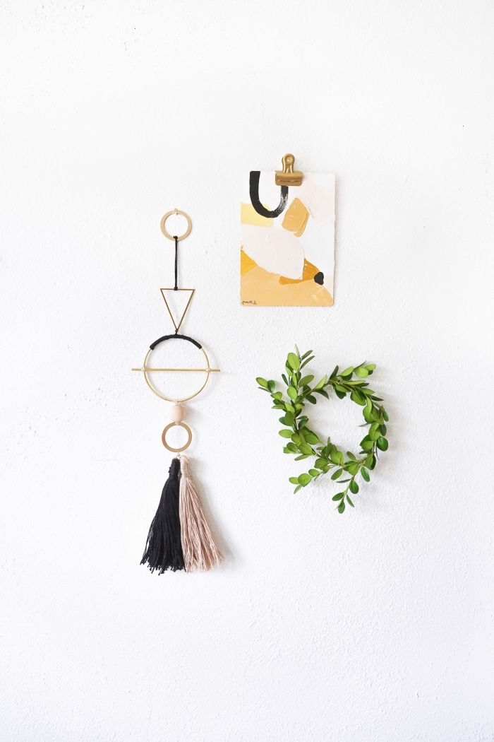 greenery wreath, beige and black macrame tassel, abstract drawing, hanging on a white wall, diy wall art