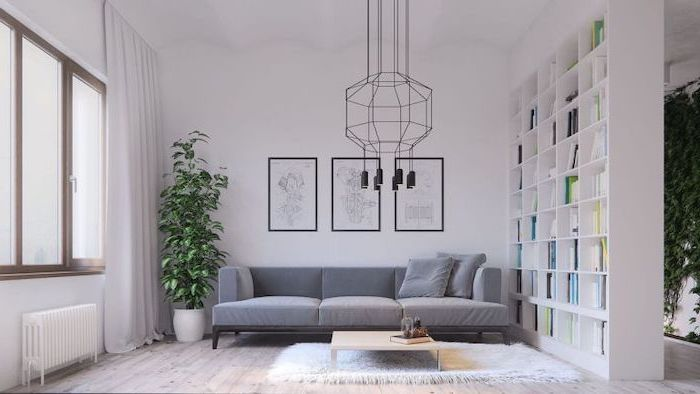 grey velvet sofa, living room arrangements, white wooden bookshelf, hanging art, wooden floor