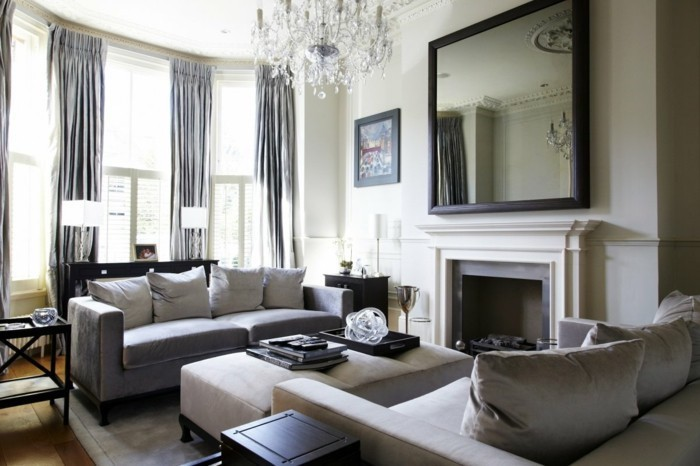 large mirror above the fireplace, grey sofas, tall windows, gray bedroom walls, white ottoman