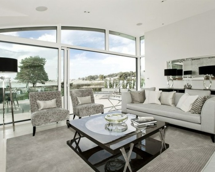large tall windows, glass coffee table, grey leather sofa, grey armchairs, gray bedroom walls