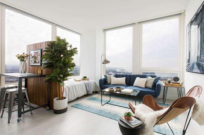 blue sofa, large windows, wooden room divider, wooden floor, living room arrangements, small metal coffee table