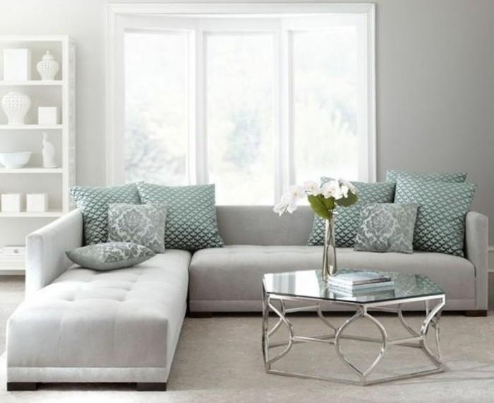 light grey corner sofa, turquoise printed throw pillows, gray bedroom walls, glass coffee table