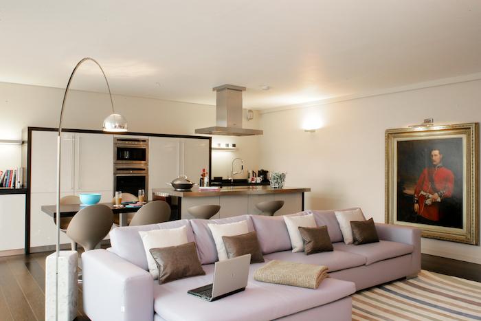 light purple corner sofa, wooden floor, living room arrangements, leather throw pillows, white kitchen
