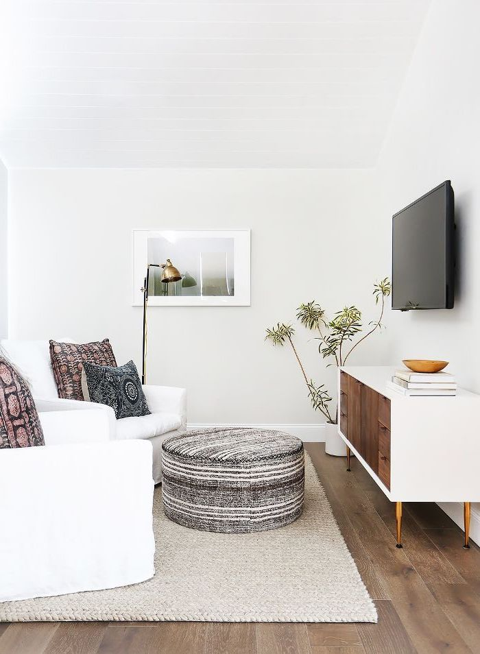 white armchairs, wooden floor, patterned throw pillows, white and wooden cabinet, small apartment decorating ideas