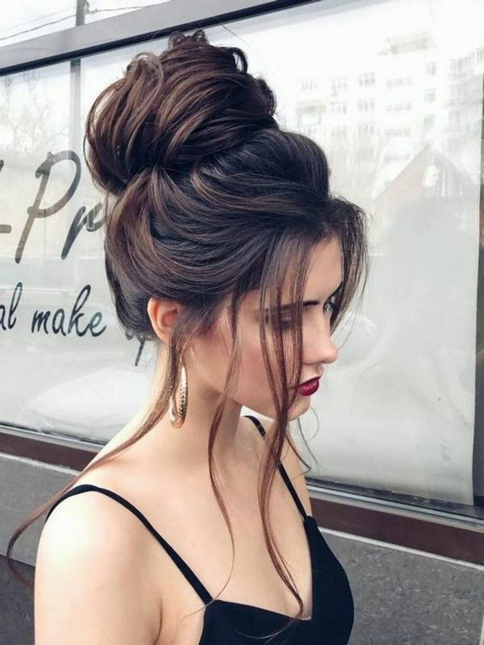 black hair, in a high messy updo, short prom hairstyles, woman wearing a red lipstick, black top