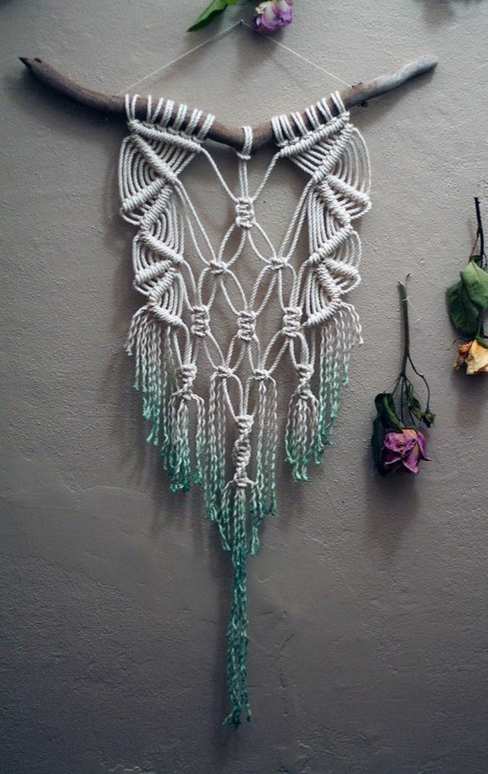 white macrame, hanging off a tree branch, on a grey wall, big wall decor, dried flowers around