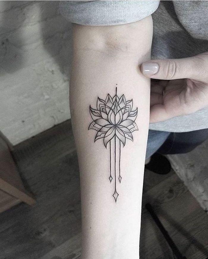 lotus flower, mandala meaning, forearm tattoo, wooden floor, grey blouse