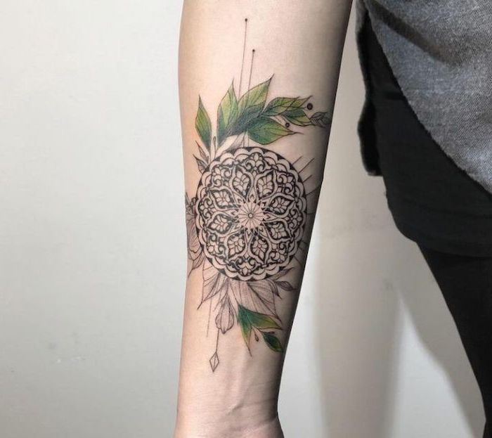 grey sweater, black pants, white background, what does mandala mean, forearm tattoo