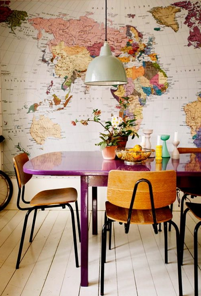 map of the world wallpaper, purple wooden table, center table decor, wooden chairs, potted flowers, candle holders