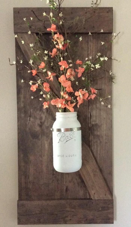 white mason jar, stuck to a wooden block, cute wall decor, orange flower bouquet inside
