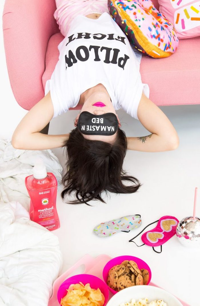 woman laying, on a pink sofa, namaste in bed, black sleeping mask, birthday gift ideas, laundry detergent