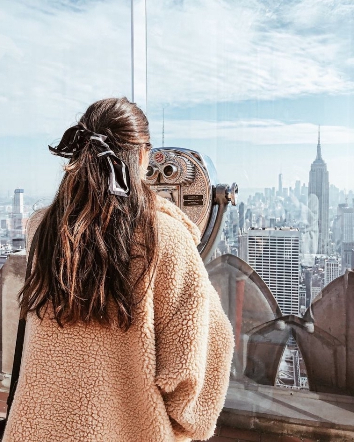 new york city skyline, long brown wavy hair, with highlights, bridesmaid updos, girl wearing an orange jacket