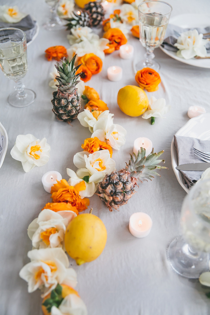 pineapples and lemons, white and orange flowers, table runner, candle decoration, candles scattered