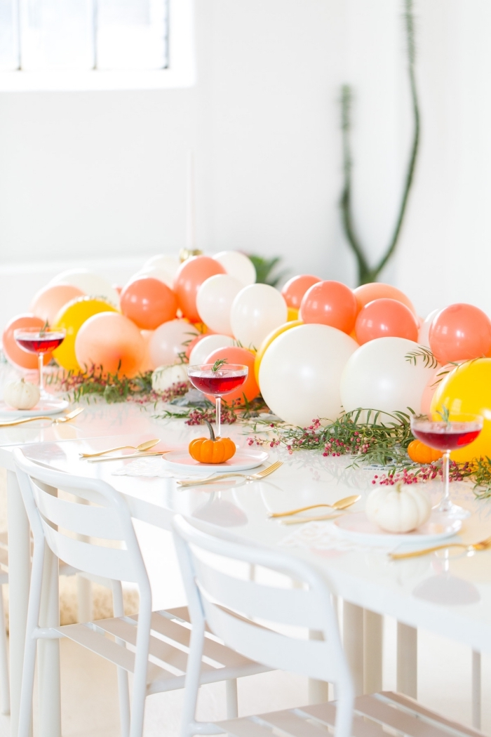 centerpiece ideas, orange white and yellow balloons, table runner, white table, wine glasses, orange white pumpkins