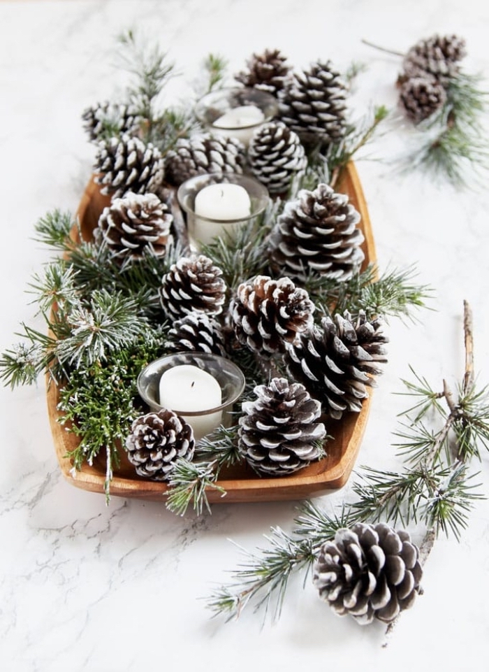marble countertop, fall flower arrangements, wooden tray, full of pine cones, candles in candle holders