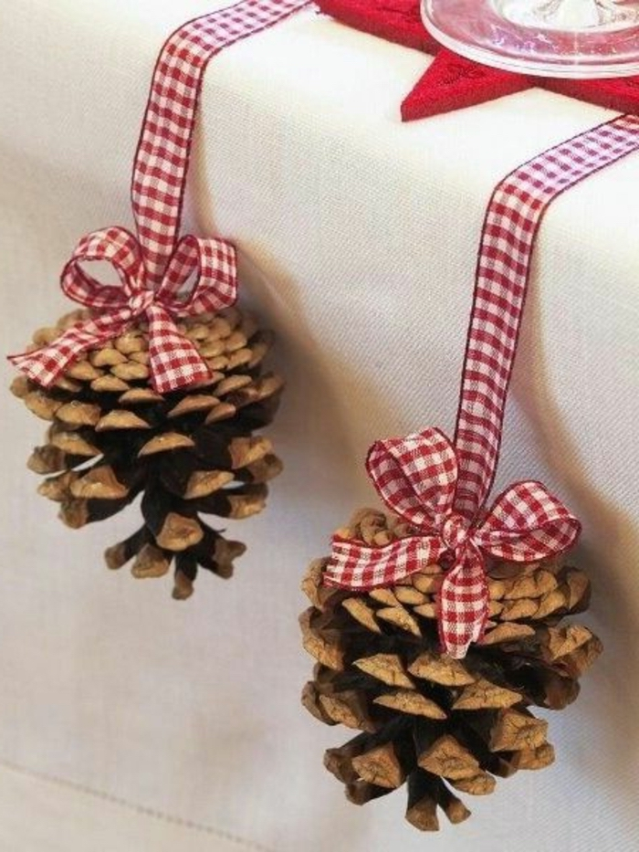 two pine cones, hanging from the table, tied with red and white, plaid ribbons, center table decor