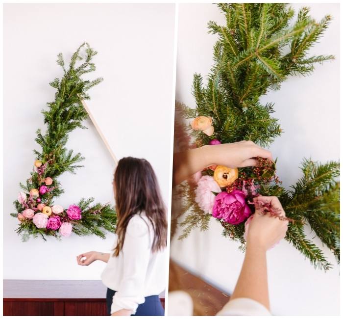 diy canvas art, wooden triangle, covered in pine tree branches, colourful flowers, hanging on a white wall