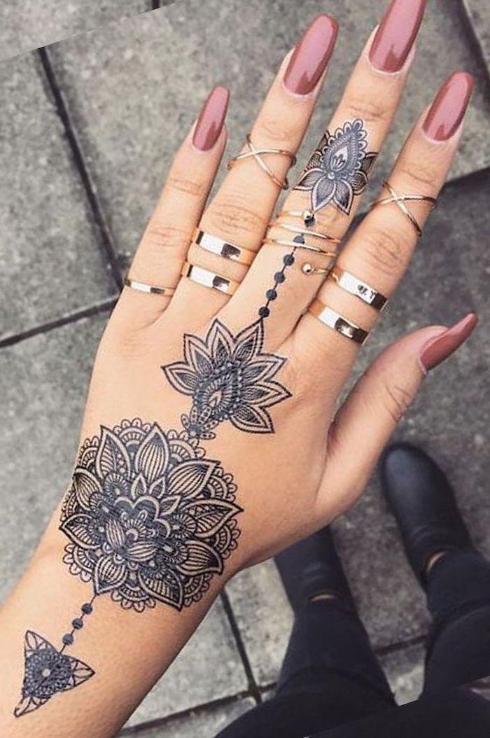 pink nail polish, silver rings, hand tattoo, mandala tattoo meaning, paved street