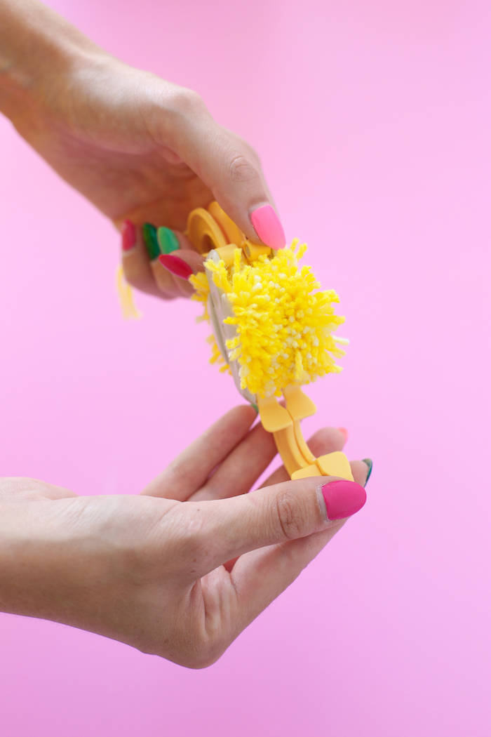 pink background, diy anniversary gifts for him, yellow yarn, pom pom maker, step by step, diy tutorial