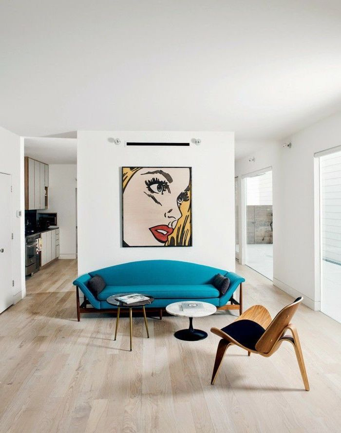 how to decorate a living room, blue sofa, hanging pop art, wooden floor, small metal coffee tables, white walls