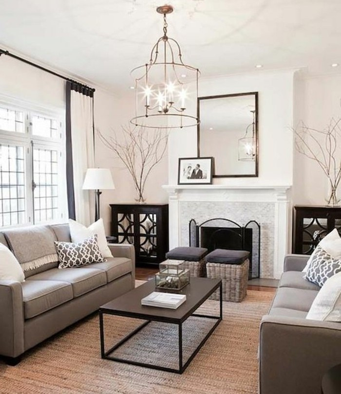 gray color schemes, mirror above the fireplace, black metal coffee table, grey sofas, tall ceiling