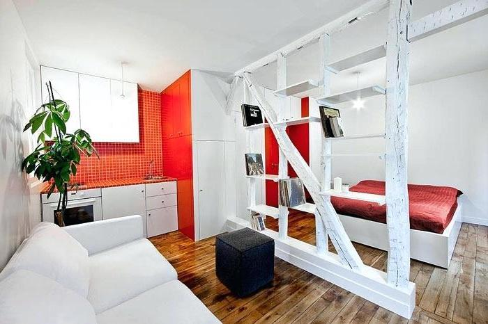orange accent kitchen wall, wooden floor, small living room layout, wooden bookshelf, room divider, white sofa