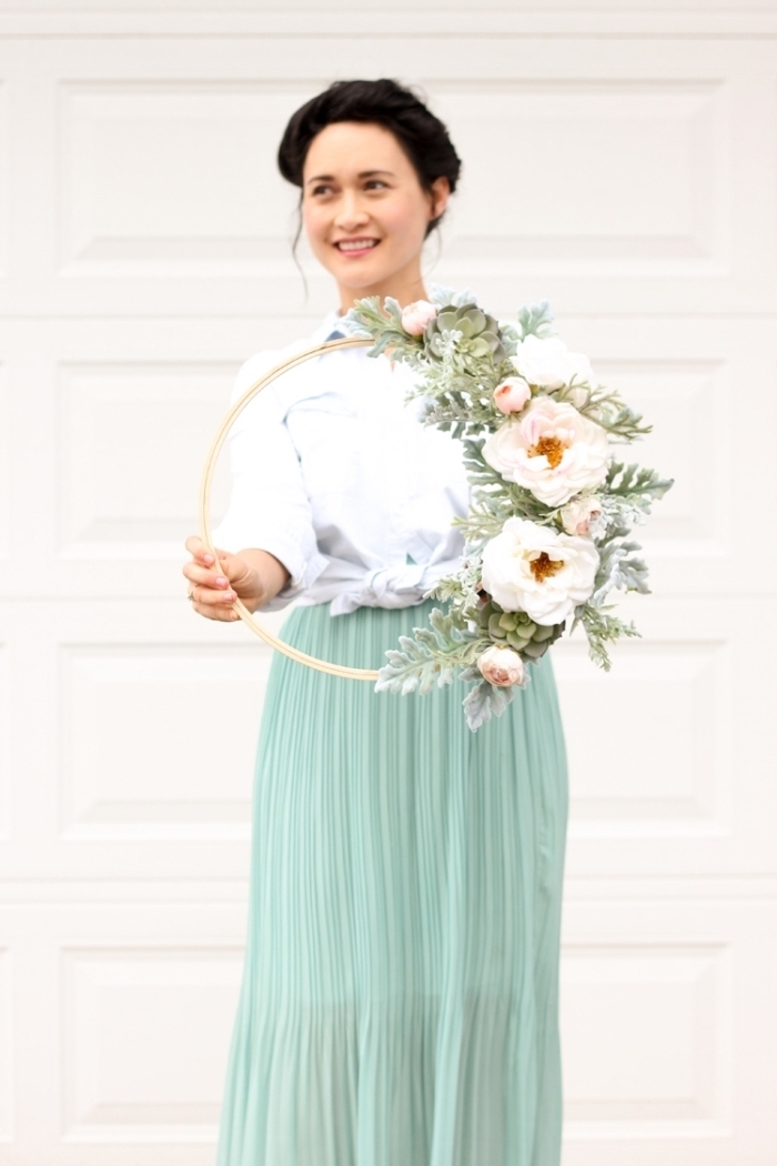 woman wearing a turquoise skirt, white shirt, holding a flower wreath, bedroom wall decor ideas