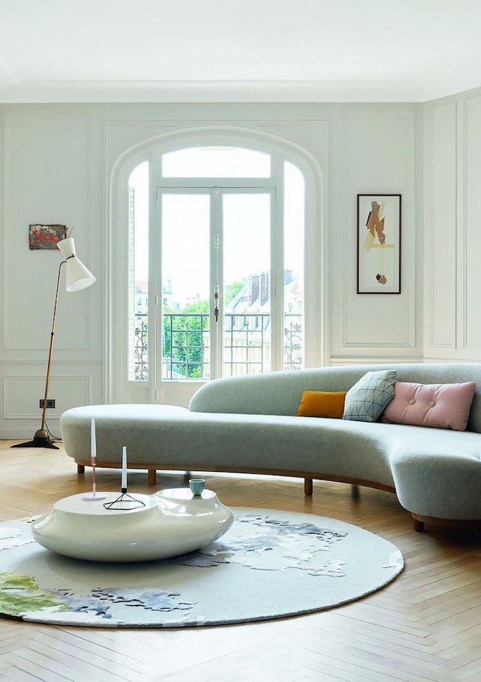 round blue sofa, wooden floor, small living room ideas, white walls, white ceramic coffee table