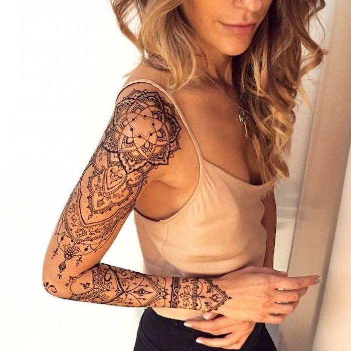 blonde hair, white top, black pants, sleeve tattoo, mandala thigh tattoo, white background