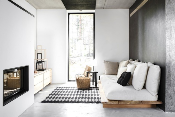 white pallet couch, couches for small living rooms, printed rug, black cement accent wall, large window
