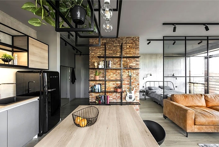 brick accent wall, brown velvet couch, glass divider, small apartment living room ideas, wooden kitchen island