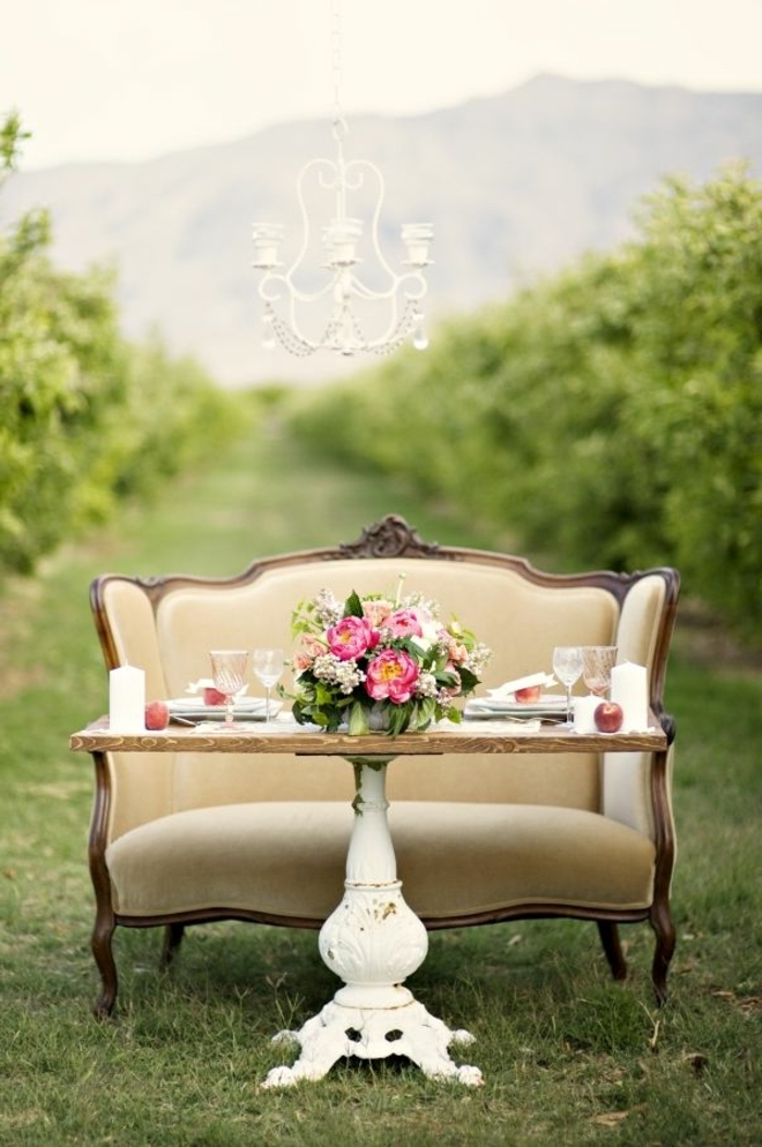 vintage wooden table, vintage sofa, simple centerpieces, large bouquet of flowers, in the middle