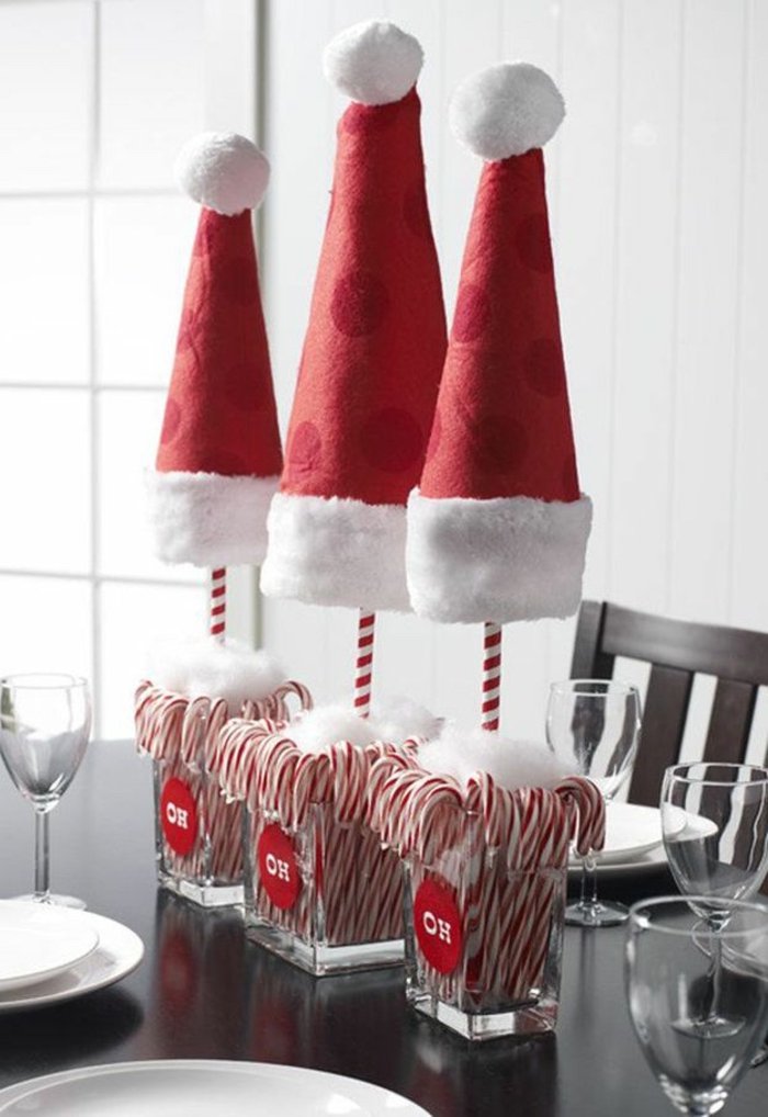 small square glass vases, full of candy canes, simple centerpieces, christmas hats, wooden table and chairs