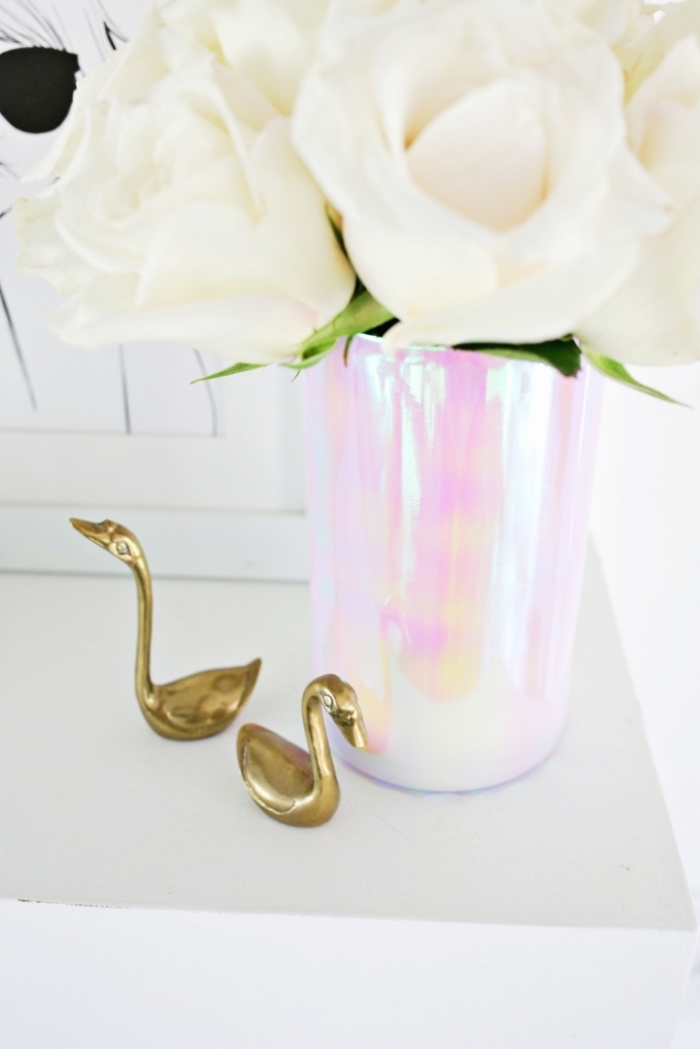 metal swan figurines, monochromatic vase, table setting ideas, bouquet of white roses, framed drawing