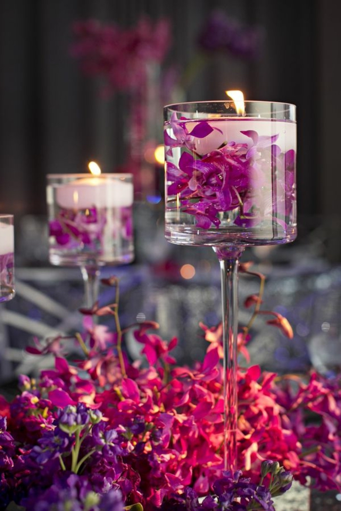 tall glass vases, filled with water, flower petals and candles, spring flower arrangements, pink and purple flowers