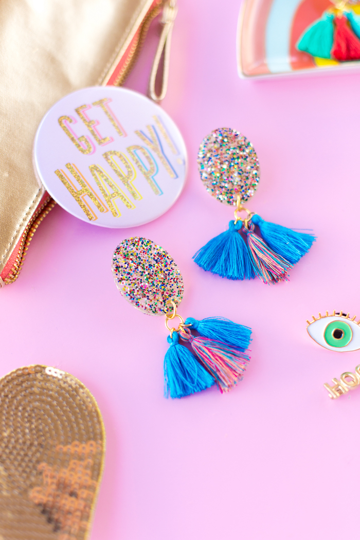 get happy badge, colourful tassel earrings, colourful glitter, creative gift ideas, pink background