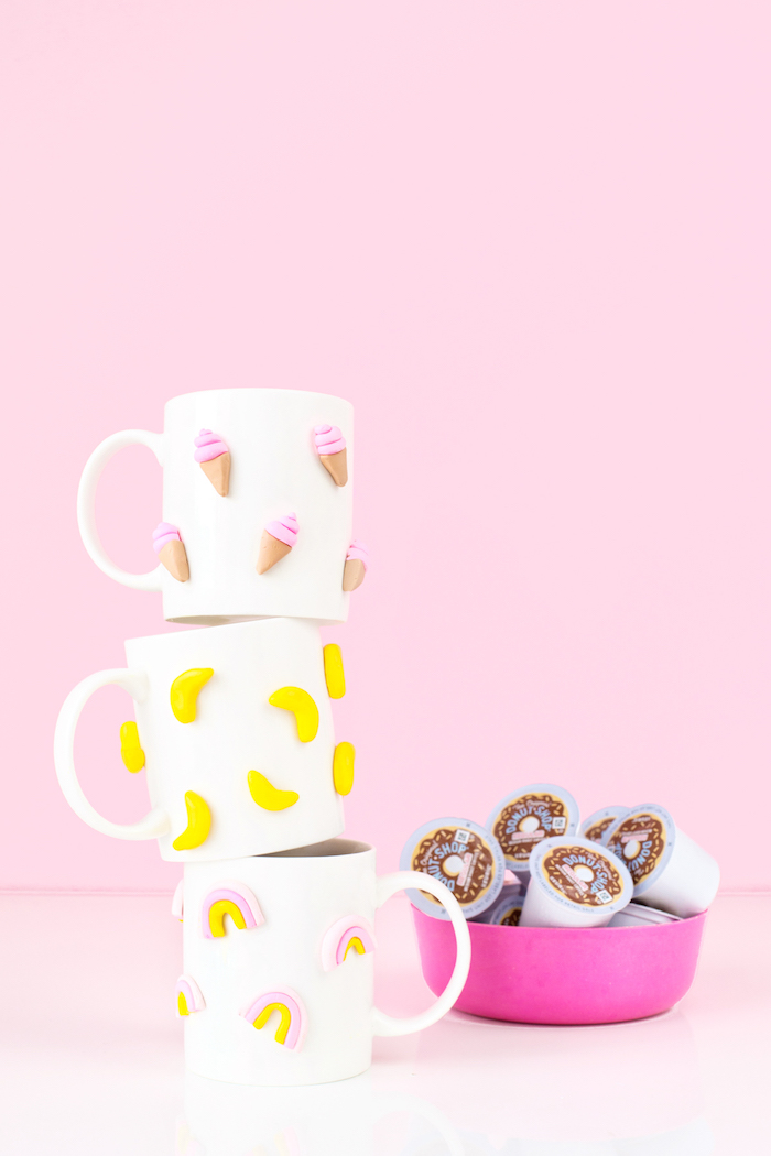 pink background, stack of white coffee mugs, diy gifts for friends, ice cream bananas and rainbow figurines