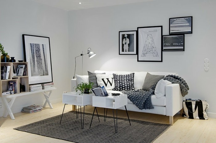 white sofa, framed hanging art, grey carpet, gray color schemes, white small coffee tables, wooden floor