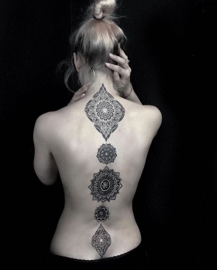 black background, back tattoo, blonde hair, small mandala tattoo