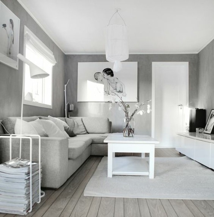 grey walls, white wooden coffee table, grey corner sofa, wooden floor, hanging photos, gray color schemes