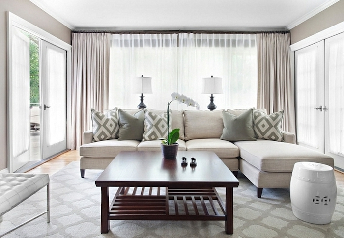 white corner sofa, wooden table, small living room furniture arrangement, tall windows, printed carpet