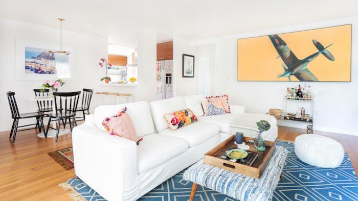 white corner sofa, blue carpet, white and blue ottomans, wooden tray, small living room furniture arrangement