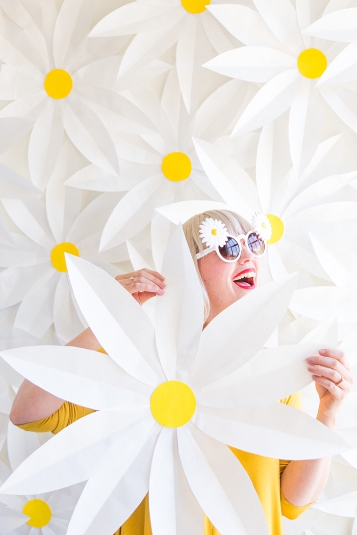 lots of white daisies, attached to a wall, woman holding a daisy, wall decor ideas, daisy sunglasses