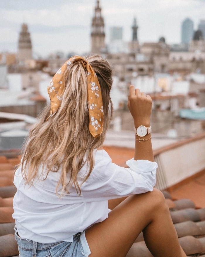 large orange floral bow, blonde wavy hair, woman wearing a white shirt and denim shorts, hairdos for long hair