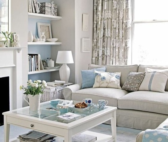 grey sofa, blue printed throw pillows, gray color schemes, glass coffee table, hanging shelves
