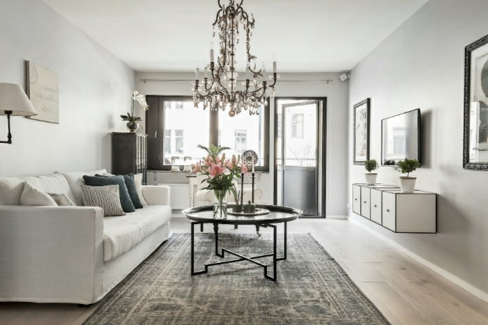 grey living room furniture, hanging chandelier, white sofa, black metal coffee table