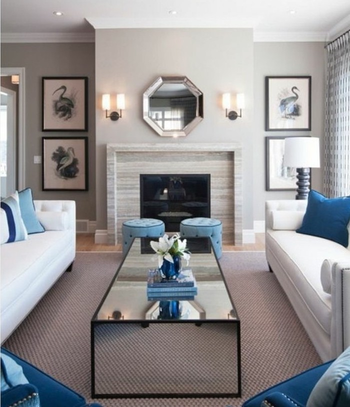 white sofas, blue printed throw pillows, blue ottomans and armchairs, grey living room furniture, glass coffee table